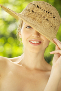 Portrait of young woman in straw hat outdoorsの写真素材 [FYI02116227]