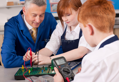 Teacher watching students working on electronic device in vocational classの写真素材 [FYI02116255]