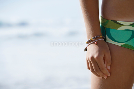 Young woman standing on beach, wearing green bikini, mid-section, close-up, front viewの写真素材 [FYI02116261]