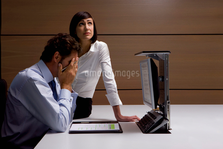 Worried businessman and businesswoman working at desk in officeの写真素材 [FYI02116278]