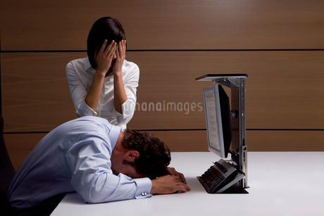 Exhausted businessman and businesswoman at desk in officeの写真素材 [FYI02116297]
