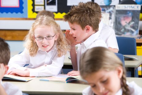 School boy whispering to girl in classroomの写真素材 [FYI02116337]