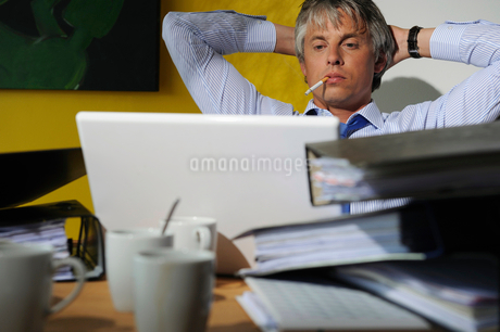 Portrait of man sitting at desk working on computerの写真素材 [FYI02116368]