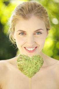 Portrait of young woman holding heart shape leaf on a stickの写真素材 [FYI02116371]