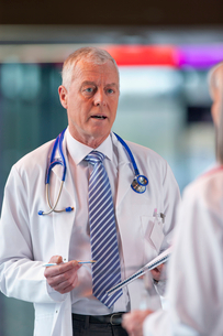 Doctors looking at paperwork together in hospital hallwayの写真素材 [FYI02116373]