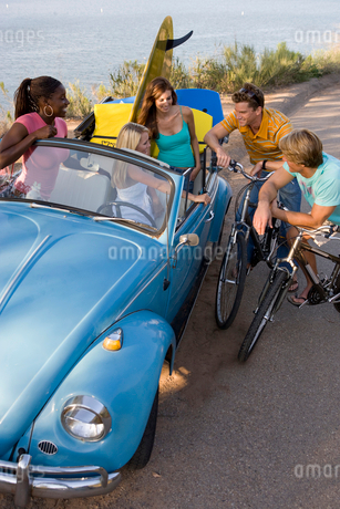 Men on bicycles in conversation with women in convertible carの写真素材 [FYI02116385]