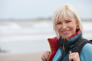 Mature Woman Walking Along Beach With Rucksackの写真素材 [FYI02116386]