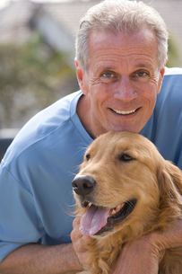 Active senior man, in blue t-shirt, crouching beside golden retriever, smiling, close-up, front viewの写真素材 [FYI02116390]