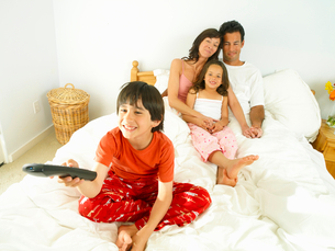 Family of four in bed, boy (8-10) with remote control, smilingの写真素材 [FYI02116407]