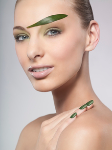 A woman wearing green nail polish and green leaf eyebrowの写真素材 [FYI02116432]