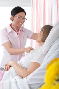 Nurse listening to patient's heartbeat in hospital roomの写真素材 [FYI02116465]