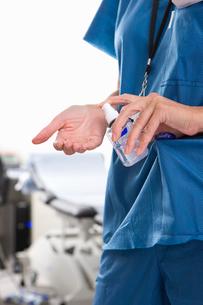 Nurse applying hand sanitizer in hospitalの写真素材 [FYI02116511]