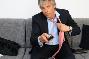 Portrait of businessman relaxing on couch holding remote controlの写真素材 [FYI02116545]