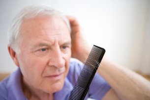Senior man with comb, close-upの写真素材 [FYI02116554]
