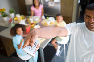 Man using remote control, family at breakfast table in backgroundの写真素材 [FYI02116559]