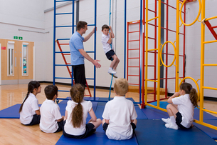 Gym teacher in school gymnasium with students demonstrating rope climbingの写真素材 [FYI02116589]