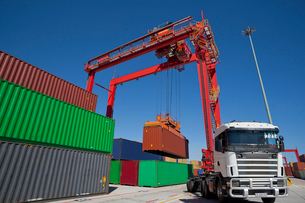 Crane loading cargo container onto lorry at commercial dockの写真素材 [FYI02116592]