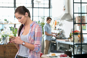 Woman text messaging with cell phone in kitchenの写真素材 [FYI02116601]