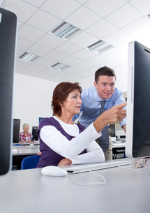 Teacher talking with adult student in college evening class computer labの写真素材 [FYI02116610]