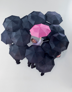 Portrait of smiling woman holding pink umbrella among black umbrellasの写真素材 [FYI02116613]