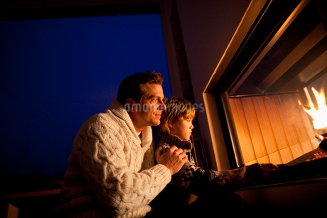 Father and son sitting near fireplaceの写真素材 [FYI02116617]