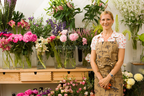 Florist in apron standing in front of display in flower shop, smiling, front view, portraitの写真素材 [FYI02116640]