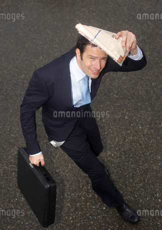 A businessman shielding his head from the rain with a newspaperの写真素材 [FYI02116642]