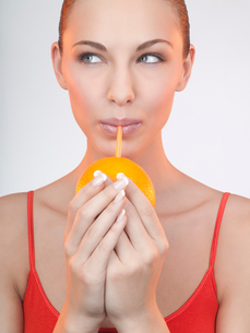A woman drinking juice from an orange with a strawの写真素材 [FYI02116648]