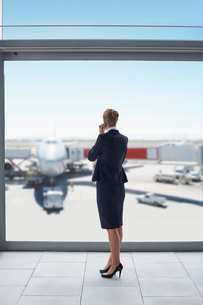 Businesswoman in suit talking on cell phone at airport windowの写真素材 [FYI02116665]
