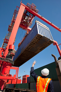 Worker guiding crane lifting cargo container at commercial dockの写真素材 [FYI02116690]