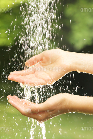 Close-up of young woman washing hands outdoorsの写真素材 [FYI02116720]