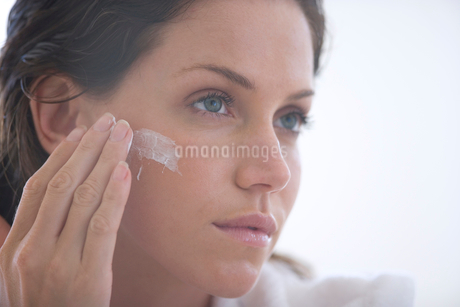 Young woman applying cream to face, close-upの写真素材 [FYI02116725]