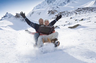 Senior couple sledding in mountains on winter dayの写真素材 [FYI02116739]