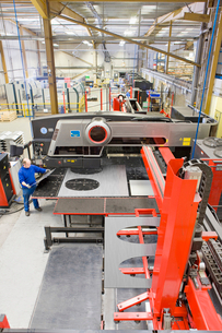 Man standing by sheet metal press in factoryの写真素材 [FYI02116741]