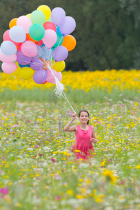 Portrait of smiling girl holding bunch of balloons among wildflowers in sunny meadowの写真素材 [FYI02116760]