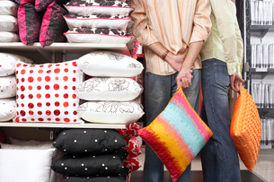 Couple standing beside shelf in shop, carrying orange cushions, hands behind back, rear viewの写真素材 [FYI02116766]