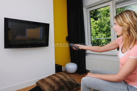 Portrait of young woman turning on televisionの写真素材 [FYI02116768]