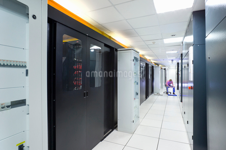 Technician with digital tablet checking cabling under floor of data centre server roomの写真素材 [FYI02116774]