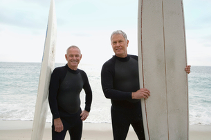 Male surfers in wetsuits with surfboards on beach, portraitの写真素材 [FYI02116775]