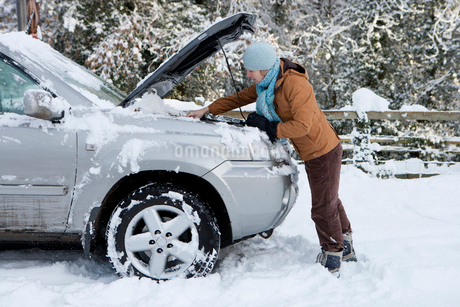 Woman standing in snow checking underneath car's hoodの写真素材 [FYI02116786]