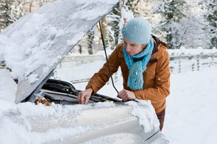 Woman standing in snow checking underneath car's hoodの写真素材 [FYI02116793]