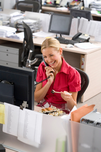Businesswoman eating at desk in office, using telephone, smiling, elevated viewの写真素材 [FYI02116801]