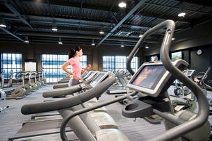Woman running on treadmill in health clubの写真素材 [FYI02116842]
