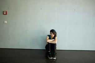 Sullen teenage girl sitting on floor in barren roomの写真素材 [FYI02116858]
