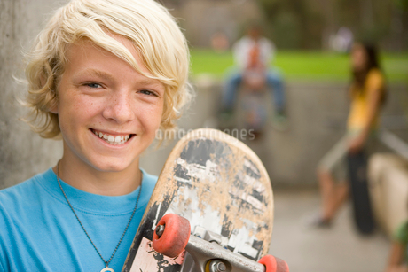Boy (11-13) with skateboard by friends outdoors, portrait, close-upの写真素材 [FYI02116862]
