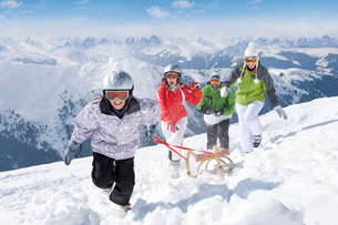 Smiling family pulling sled in snow on ski slopeの写真素材 [FYI02116874]