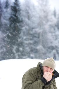 Mid adult man warming hands in snowy weatherの写真素材 [FYI02116881]