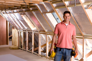 Smiling electrician standing in attic under constructionの写真素材 [FYI02116893]