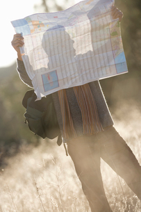 Hiker in field looking at mapの写真素材 [FYI02116917]
