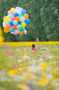 Girl holding bunch of balloons among wildflowers in sunny meadowの写真素材 [FYI02116933]